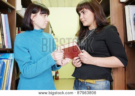 Woman librarian gives the female student a book