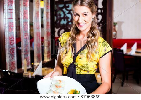 Waitress with sushi in asian restaurant