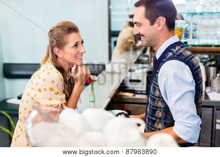 Girl in cafe or coffee bar flirting with barista who is busy preparing Cappuccino with professional machine