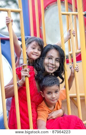 Asian mother with two young children in the playground