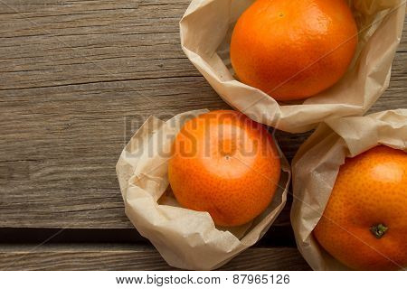 Three Tangerines Wrapped In Paper On Wooden Background