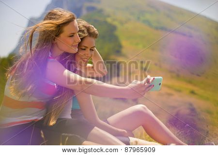 Two girls taking picture with smartphone