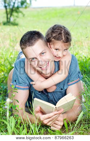 Nice day in nature, father and daughter relaxing reading book in nature