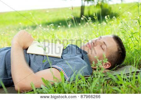 Young handsome man relaxing in park, he is sleeping with book in hands