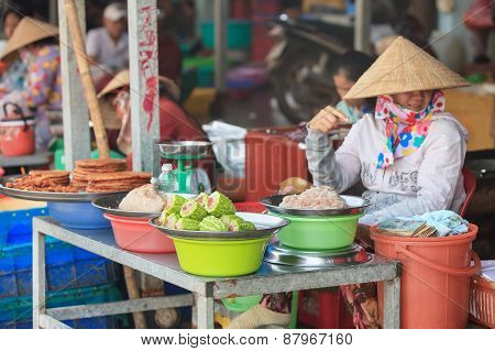 VIETNAM - DECEMBER 2014: Traditional asian market saleswoman in conical hat at the stall