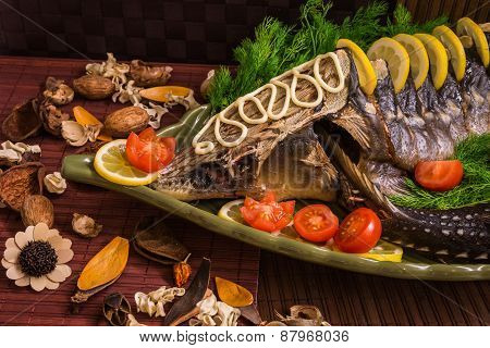 Sturgeon Decorated With Lemon And Tomatoes On A Green Plate