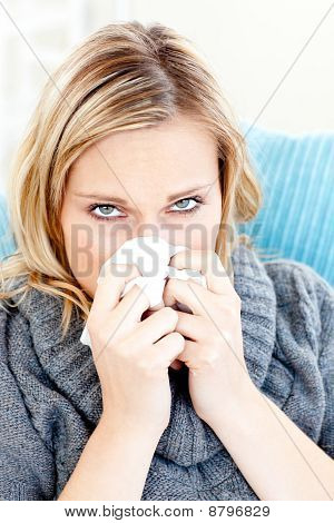 Sick Woman Using A Tissue Sitting On A Sofa