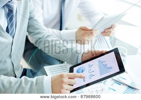 Electronic data analysis in touchpad and hand of businessman pointing at document while explaining it