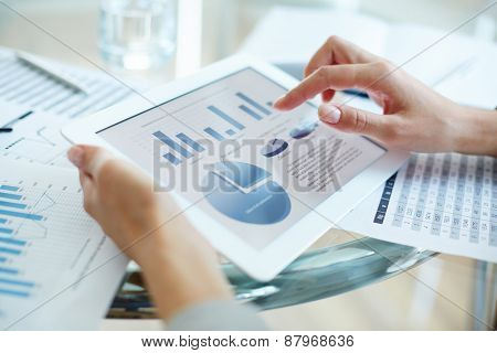 Financial report in touchpad and hand of businesswoman over it