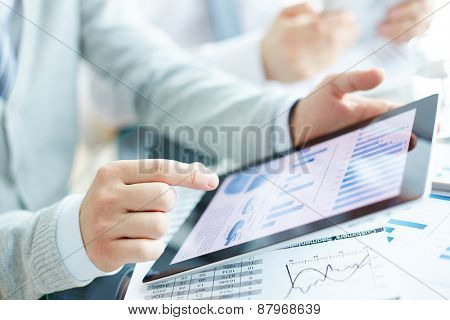 Electronic document in touchpad and hand of businessman pointing at it