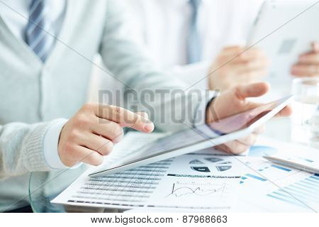 Businessman hand pointing at touchpad at workplace