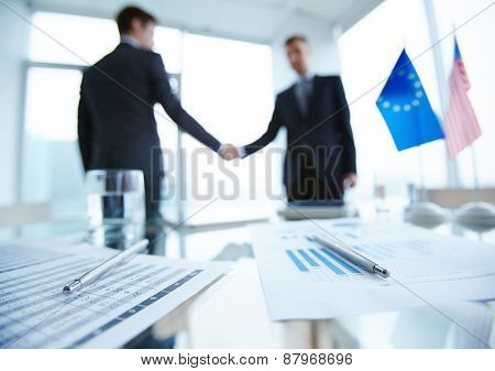Business documents and pens on workplace with two men handshaking on background