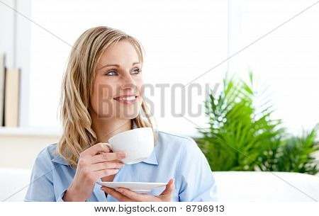Captivating Businesswoman Holding A Cup Sitting On A Sofa