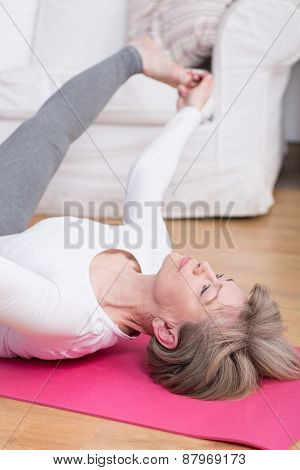 Lady Stretching On The Floor Mat