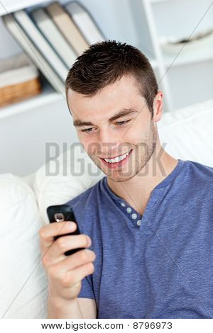 Charming Young Man Sending A Text And Smiling In The Living-room