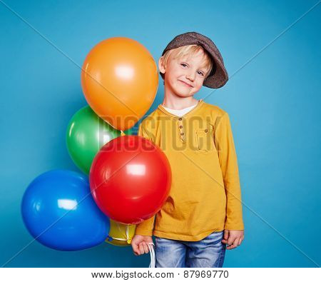 Cute lad with multi-color balloons looking at camera