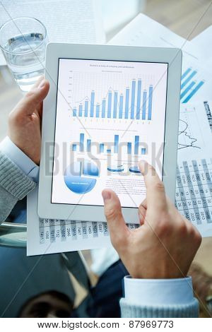 Electronic data and hand of businessman pointing at touchscreen