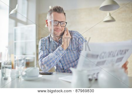 Confident businessman in eyeglasses talking on cellphone while reading newspaper