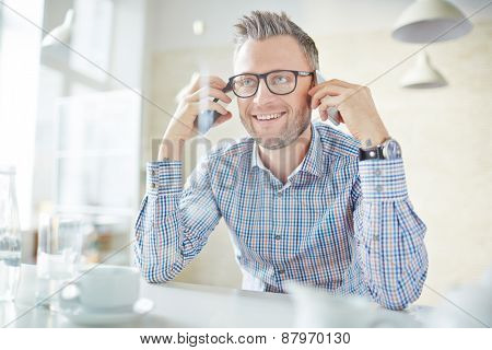Smiling businessman in eyeglasses holding two smartphones by ears