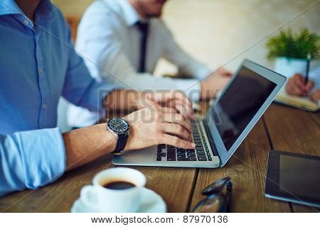 Male hands typing on laptop keypad in working environment