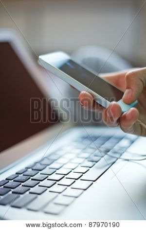 Smartphone in male hand over laptop keypad