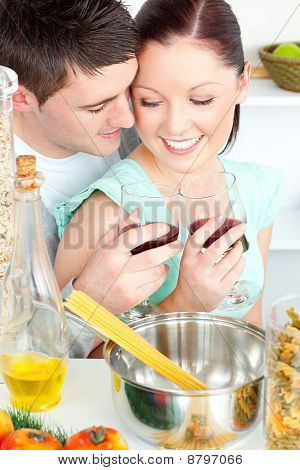 Loving Couple Preparing Spaghetti In The Kitchen And Drinkng Wine