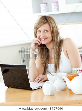 Smiling Woman Having Breakfast And Using Her Laptop Looking At The Camera