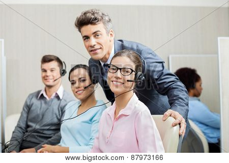 Portrait of confident manager with team in call center