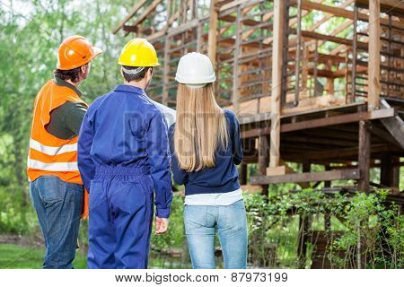 Rear view of male and female engineers examining incomplete wooden cabin at construction site