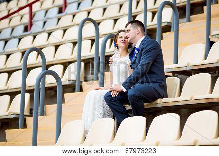 Beautiful couple sitting and watching football game stadium stand