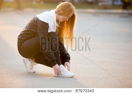 Sporty Girl Fixing Laces On Sneakers