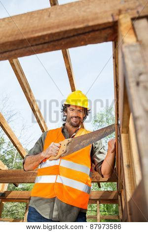 Low angle portrait of smiling worker cutting wood with handsaw at construction site