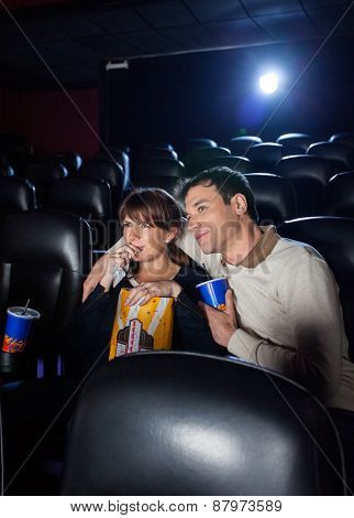 Mid adult couple having snacks while watching movie in cinema theater