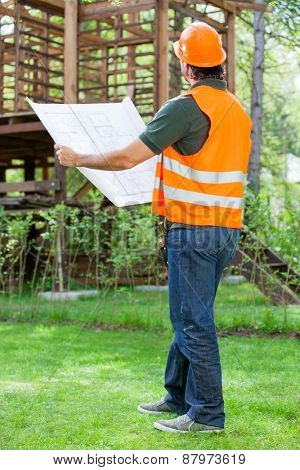 Full length of male engineer holding blueprint while examining wooden cabin at construction site