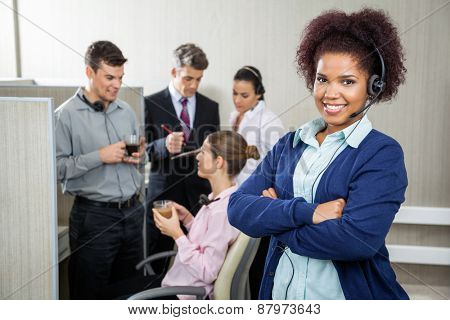Portrait of female customer service representative standing arms crossed while team discussing in background at call center