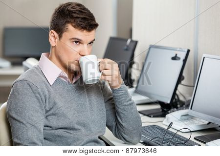 Young male customer service representative having coffee in office