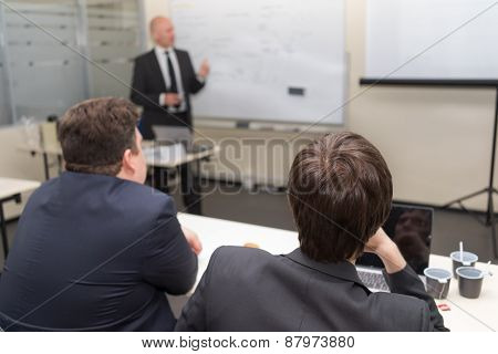 Tutor Teaching Class And Two Men Sitting At The Desk Listening