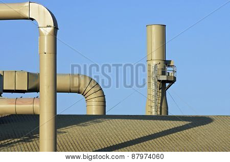 Metal pipes on the facade of a factory.