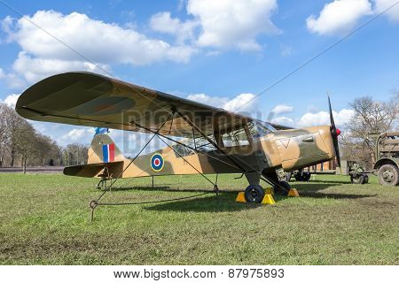 Old military airplane on green meadow with blue sky
