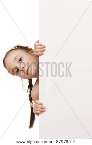 portrait of a posing young girl holding empty white board isolated over white