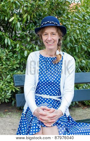 Woman in old-fashioned dress sitting on bench in park
