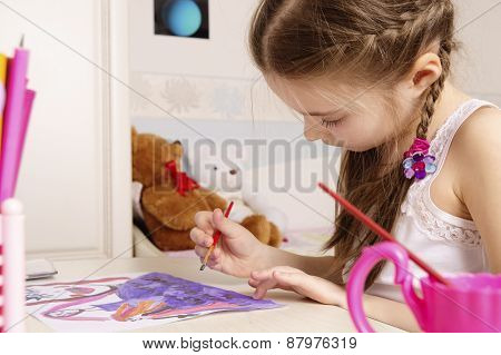 portrait of a young girl drawing a picture in her playroom