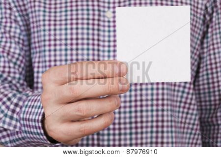 abstract man in check shirt holding white card