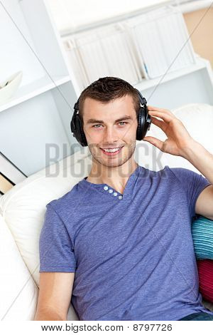 Relaxed Young Man Listening To Music With Headphones Looking At The Camera In The Living-room