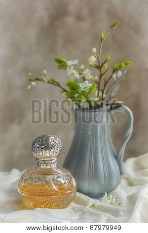 Antique perfume bottle with antique jug filled with spring blossom