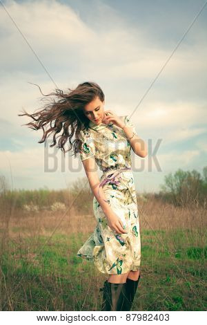 young woman in summer dress in grass field, hair in motion from wind, retro look and colors