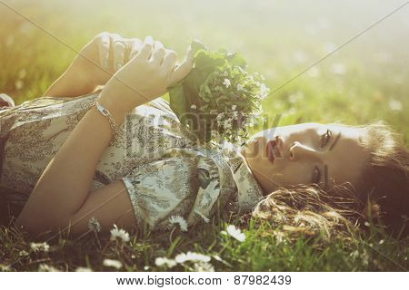 delicate beautiful young woman enjoy in sun lie in grass hold bouquet of wild flowers retro look and colors