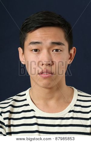 Pleased young Asian man looking at camera