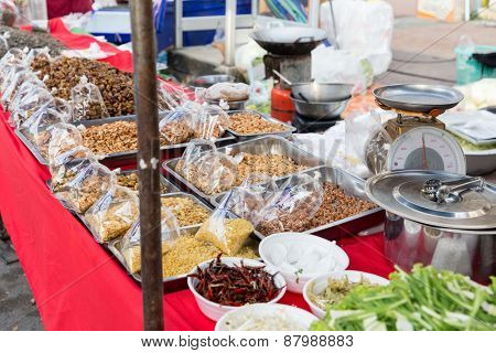 cooking, asian kitchen, sale and food concept - nuts and spices at street market