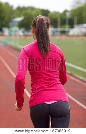 fitness, sport, training, people and lifestyle concept - african american woman running on track outdoors from back